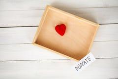 Donaciones y caridad Concepto de la donación Caja de donaciones y de corazón en el fondo blanco fotos de archivo