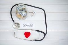 Donaciones y caridad La inscripción dona Concepto de la donación Vidrio con donaciones en el fondo blanco Caridad y dinero imágenes de archivo libres de regalías