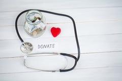 Donaciones y caridad La inscripción dona Concepto de la donación Vidrio con donaciones en el fondo blanco Caridad y dinero imagen de archivo