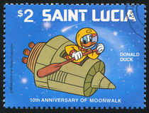 Donald Duck paddling satellite. SAINT LUCIA - CIRCA 1980: stamp printed by Saint Lucia, shows shows Walt Disney Characters, Space scenes, Donald Duck paddling royalty free stock image