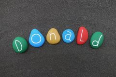 Donald, masculine name with multicolored stones over black volcanic sand. Celebration of Donald masculine name with multicolored stone letters over natural Stock Photo