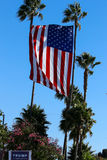 Donald Trump sign and United States Flag. A property in Huntington Beach CA USA is pro Trump displaying signs and a beautiful huge USA flag between two tall palm royalty free stock photo