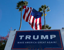 Donald Trump sign and United States Flag. A property in Huntington Beach CA USA is pro Trump displaying signs and a beautiful huge USA flag between two tall palm stock photography