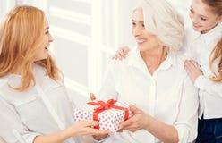 Donante de emisión de la abuelita y de la nieta presente a la madre sorprendida Fotos de archivo
