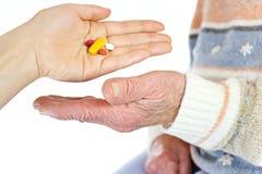 Donante de píldoras a la mujer mayor Fotografía de archivo libre de regalías