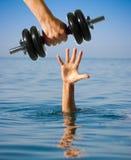 Donante de pesa de gimnasia al hombre de hundimiento en vez de la ayuda Fabricación peor Imagen de archivo