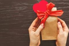 Donante de un regalo en conmemoración del día del ` s de la tarjeta del día de San Valentín Imagenes de archivo