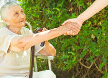 Donante de una mano amiga para una señora mayor que se sienta en el parque Imagen de archivo libre de regalías