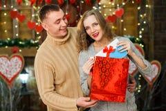 Donante del muchacho presente a su muchacha el día del ` s de la tarjeta del día de San Valentín Imagenes de archivo