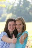 Donante hermoso entusiasta de las muchachas pulgares para arriba Imagenes de archivo