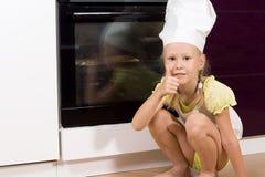 Donante lindo del cocinero de la chica joven pulgares para arriba Fotos de archivo libres de regalías