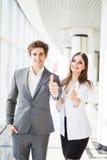 Donante motivado del hombre de negocios y de la mujer pulgares encima del gesto de la aprobación y del éxito como plantean de lad Imágenes de archivo libres de regalías