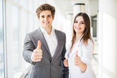 Donante motivado del hombre de negocios y de la mujer pulgares encima del gesto de la aprobación y del éxito como plantean de lad Foto de archivo