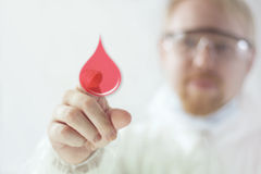 Donate Blood. Man in Lab Suit Pointing at Blood Drop Royalty Free Stock Photography