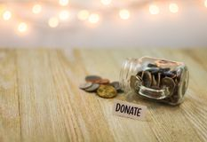 Donate money concept with shiny coins on a glass jar. Soft bokeh background on wooden board royalty free stock photos
