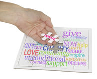 Donate to Charity Puzzle. Hand holding a jigsaw puzzle piece showing the word DONATE, the remainder of the puzzle contains a charity word cloud on white royalty free stock photography