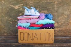 Donation box with children`s things. On wooden background Royalty Free Stock Photography