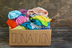 Donation box with clothes. On the old wooden background Stock Photo