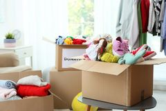 Donation box with clothes and toys on table indoors. Space for text stock image