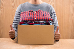 Donation box for poor with clothing in male hands.  Royalty Free Stock Images