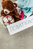 Donation box with toys, clothes and food. Plastic donation box with toys, clothes and food, white grey background copy space Royalty Free Stock Photos