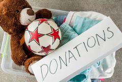 Donation box with toys, clothes and food. Plastic donation box with toys, clothes and food, white grey background copy space Stock Photo