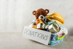 Donation box with toys, clothes and food. Plastic donation box with toys, clothes and food, white grey background copy space Stock Photography