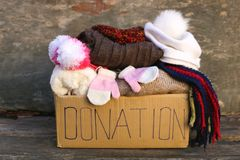Donation box with warm winter clothes. On old wooden background royalty free stock images