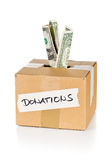Donation cardboard box with dollar banknotes. Donation carton box with dollar bills over white background Stock Images