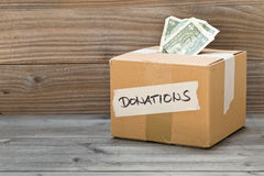 Donation cardboard box with dollar banknotes Stock Photography