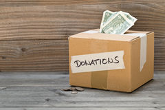 Donation cardboard box with dollar banknotes and coins. Donation carton box with dollar bills and coins on wooden table background Royalty Free Stock Image