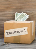 Donation cardboard box with dollar banknotes and coins. Donation carton box with dollar bills and coins on wooden table background Royalty Free Stock Photography