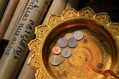 Donation. Coin in thai style golden tray. make merit, donation royalty free stock photos