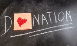 Donation. Concept on chalk table whit a red heart Royalty Free Stock Photo