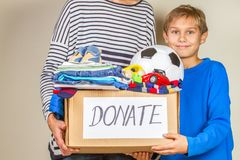 Donation concept. Donate box with clothes, books and toys in child and mother hand.  royalty free stock images