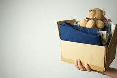 Donation concept. Hands holding donate box with clothes. Copy space royalty free stock photos