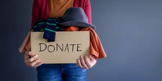 Donation Concept. Woman holding a Donate Box with full of Clothe stock image