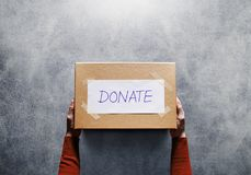 Donation Concept. Woman holding a Donate Box for Giving. Sharity activity. Top View royalty free stock photo