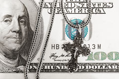 Donation. A hundred dollar bill with a silver cross on it meaning donation royalty free stock photography