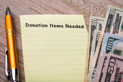 Donation Items Needed concept on notebook and wooden board stock photos
