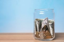 Donation jar with money on table against color background. Space for text stock photo