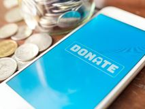 Donation money online by smart phone royalty free stock image