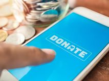 Donation money online by smart phone stock photography