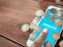 Donation money online by smart phone stock photo