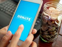 Donation money online by smartphone royalty free stock photography