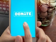 Donation money online by smartphone stock photography