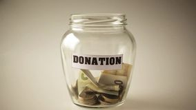 Donation, money savings in a jar. Donation, money savings dropping in a glass jar, slow motion video stock footage