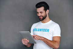 Donation by one click. Confident young man in volunteer t-shirt using his digital tablet with smile while standing against grey background royalty free stock photography