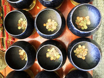 Donation. Top view the little gold coins put in row of black alms-bowls on wooden table. The merits and donation for happiness ans good luck at the buddist Stock Image