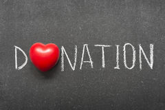 Donation. Word handwritten on school blackboard with heart symbol instead of O royalty free stock images